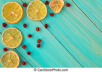 Dried oranges with ashberry on the white wooden background.