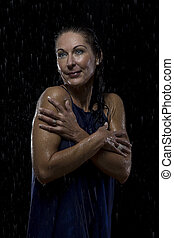 Beautiful woman in blue dress stands in rain at night