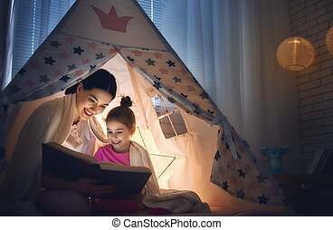 Family bedtime. Mom and child daughter are reading a book in...