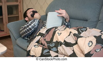Sick and tired young man using tablet in bed
