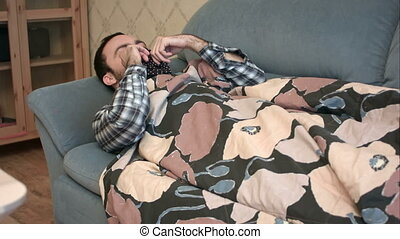 Young man pretending to be sick with flu lying on the sofa....