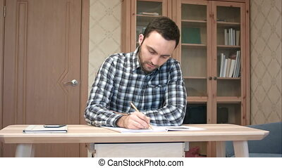 Young man taking phone call during study at home