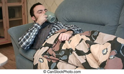 Sick young man drinking hot tea or anti-fever medicine in bed