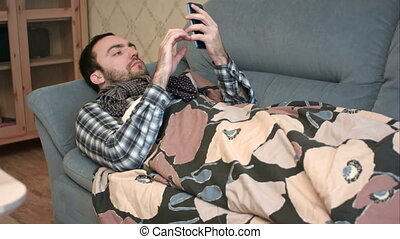Sick man in scarf lying on the sofa and using phone....