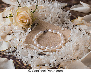 Beautiful pearl bracelet on wooden background with rose...