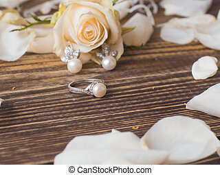 Pearl ring and earrings with white rose on dark wooden...