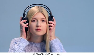 Pretty girl listening to music in headphones over a white...