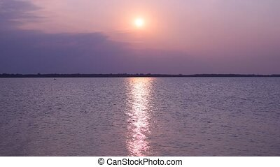 Sun shines over lake or river forming sun path on water -...