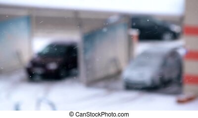 Snow falls on blurred background with cars in winter
