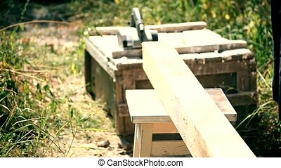 Carpenter planes a beam with electric wood planer tool...