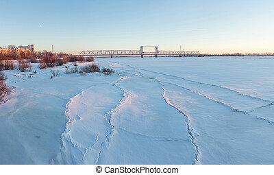 Frozen river Northern Dvina and Railway bridge in...