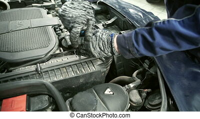 Master unscrews air filter in hood of car at service center.