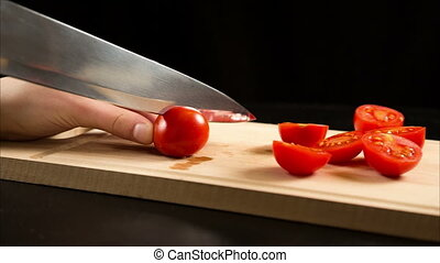 Cutting red cherry tomatoes on wooden cutting board -...