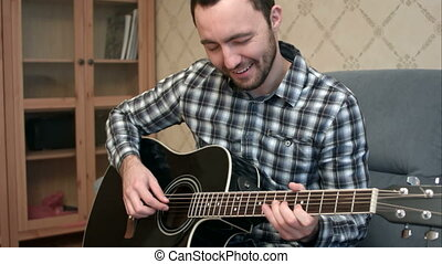 Young man playing difficult guitar piece sitting on the sofa