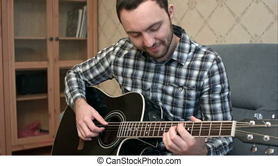 Happy young man playing the guitar while sitting on sofa at home