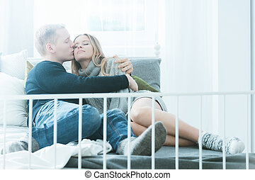 Couple relaxing in bed - Young couple relaxing in bed,...