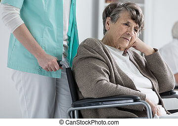 Woman on wheelchair - Thoughtful senior woman on a...