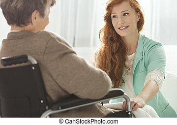 Nurse looking at elder woman - Supportive young nurse...