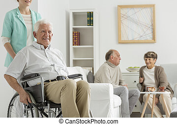 Retirement home with elder man on a wheelchair