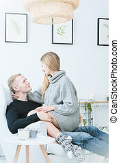 Woman relaxing with man on armchair during winter morning