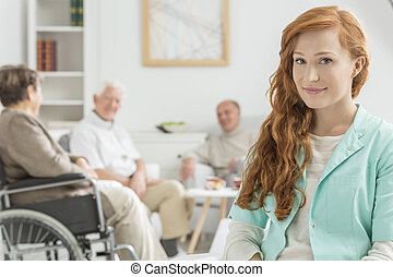Young nurse at retirement home - Young and red-haired nurse...