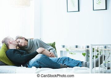 Couple embracing in bed, enjoying lazy sunday morning