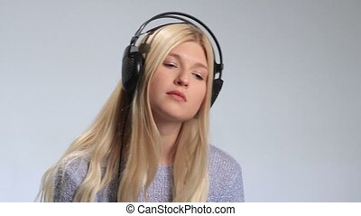 Young woman listening to melancholic music - Young...