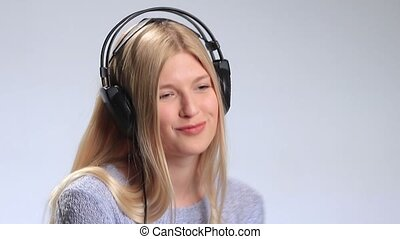 Blonde girl with headphones listening to music - Young...