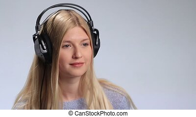 Beautiful woman listening to music in headphones