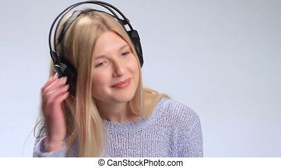 Attractive girl listening to music with headphones -...