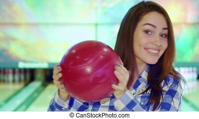 Girl holds bowling ball near her face - Gorgeous brunette...