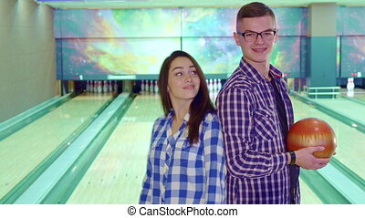 Boy and girl look at each other at the bowling