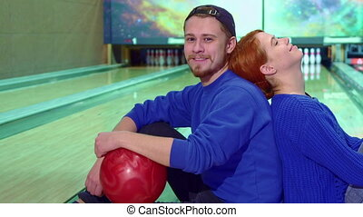 Boy and girl sitting on the floor at the bowling alley -...