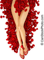 Woman legs on rose petals - Hips and legs of slim tanned...