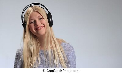Teenage girl wearing headphones listens to music - Young...