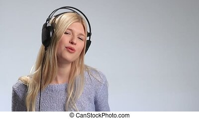 Emotional young blonde in headphones over white