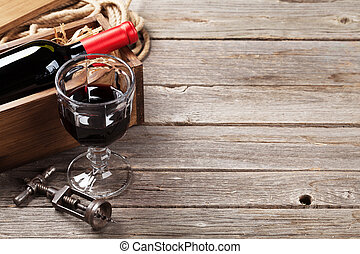 Red wine bottle and glass on wooden table. View with copy...