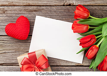 Red tulips, gift box and Valentine's day greeting card