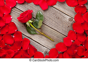 Red rose petals heart and flower over wooden table. Top view...