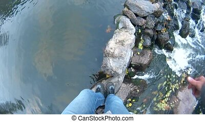 Feet of a person crossing a mountain river