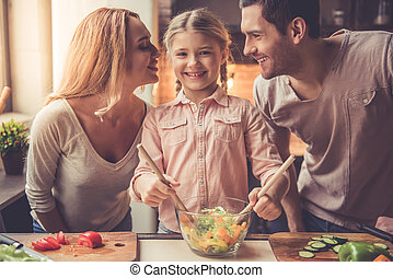 Young family cooking - Cute little girl is mixing salad and...