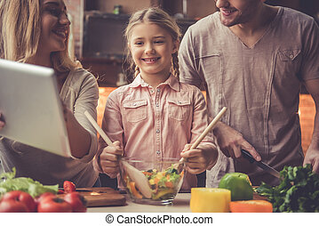 Young family cooking - Cute little girl and her beautiful...