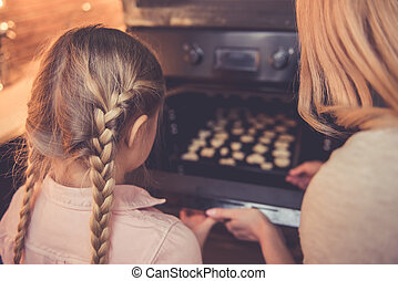 Mother and daughter baking - Back view of little girl and...