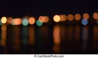 Defocused city lights over water come into focus. Small...