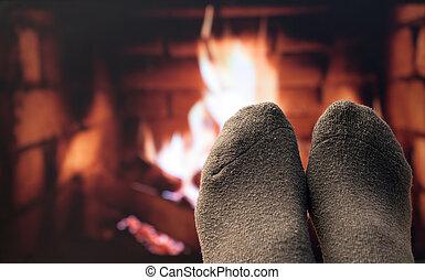 Feet in woollen socks by the fireplace.