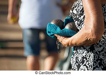 Hand of holding petanque ball,close up of people at...