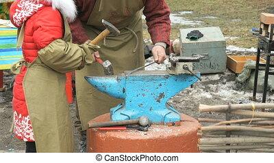 Blacksmith teaching child how to do smithing - Blacksmith...