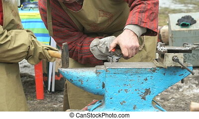 Blacksmith teaching girl how to do smithing