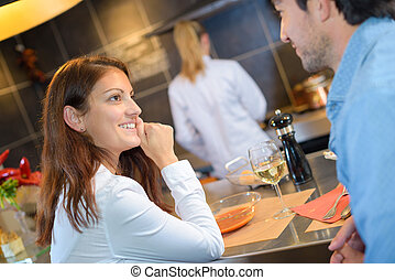 lovers sharing dinner in a professional kitchen