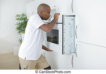 Man fitting new oven in kitchen